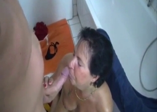 Tanned MILF licking her son's meaty balls